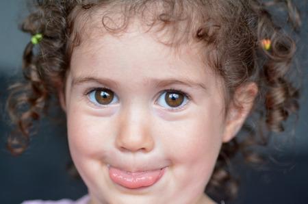 lengua afuera: rizado niño (niña 02 años de edad) que se pega la lengua hacia fuera. Educación y concepto de la infancia. Gente real. espacio de la copia