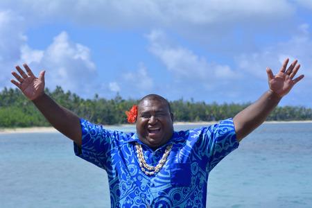 Fijian man greeting in Fijian language Bula,(general greeting hello) against The Blue Lagoon on Nanuya Lailai Island on of the Yasawa Islands of Fiji. Real people copy space Banco de Imagens
