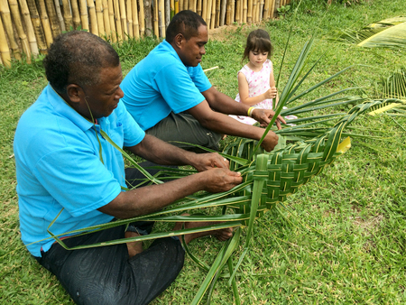 basket weaving: Fijian men teach young tourist girl how to create a basket from weaving a Coconut Palm leaves.Travel Fiji concept, Real people copy space
