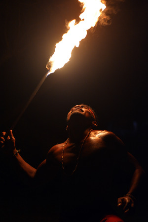 Indigenous Fijian holds a torch during a fire dance at nigh in Fiji. Real people copy space