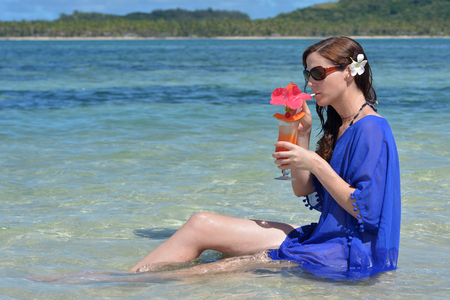 Tourist woman drinks a tropical cocktail in the waters of a resort on an island in Fiji. Travel holiday vacation concept. Real people copy space Stock Photo