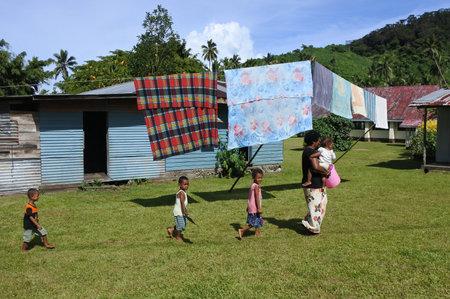 SAVUSAVU, FIJI - JAN 23 2017: Indigenous Fijian woman and her children in a local village near Savusavu in Vanua Levu Island, Fiji. The Fijian woman generally supervises the house keeping and disciplines the children.