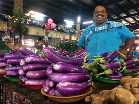 LAUTOKA, FIJI -  DEC 30 2016:Indigenous Fijian man sells Eggplants in Lautoka Market, Fiji. Fijian Eggplant exports exceeded papaya sales for the first time ever in 2015.