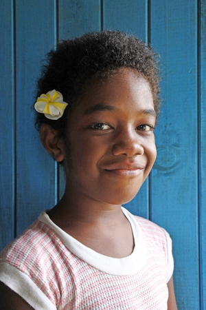 fijian: A happy young Indigenous Fijian Girl (age 8) looks at the camera and smile. Real people copy space