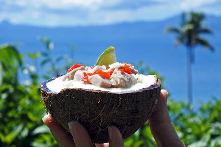 Fijiana, Kokoda (pesce crudo insalata) contro il Tropical Island paesaggio. Kokoda è la versione di Fiji di ceviche, arricchita con latte di cocco per bilanciare tutto l'acido.