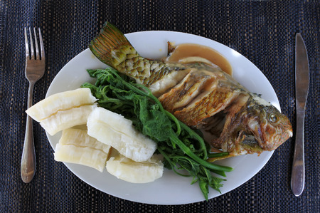 Indigenous Fijian seafood and vegetables dish in Fiji. Fried Parrotfish, tapioca and steamed pumpkin leaves.Food background