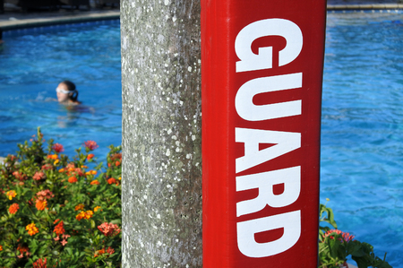 Lifeguard sign in a resort pool with a person swim in the background. Swimming safety concept.