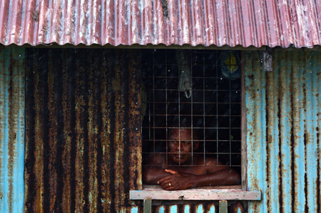 Indigenous Fijian man looks out of the window during a Tropical Cyclone storm. Stock Photo
