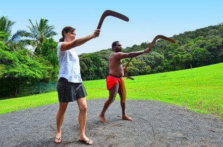 teaches: Yirrganydji Aboriginal warrior teaches a young woman how to throw a boomerang during cultural show in Queensland, Australia.