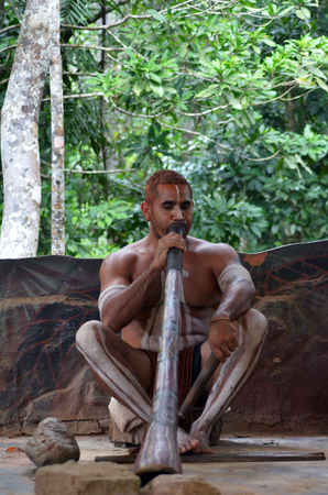 Portrait of one   Yirrganydji Aboriginal man play Aboriginal music on didgeridoo, instrument during Aboriginal culture show in Queensland, Australia. Stock Photo - 77867904