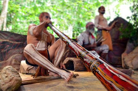 Yirrganydji Aboriginal men play Aboriginal music on didgeridoo and wooden instrument during Aboriginal culture show in Queensland, Australia.