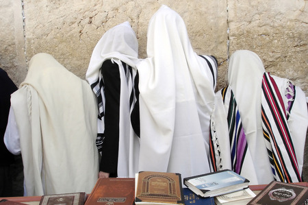 worshipping: JERUSALEM - APRIL 07: Orthodox Jewish men Pray at the Western Wall during the Jewish holiday of Passover in Jerusalem, Israel. Passover commemorates the liberation of the Israelites from Egyptian slavery Editorial