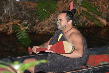 treaty: ROTORUA, NZL - APR 25 2017:Maori man in traditional waka boat.Maori are the indigenous people of New Zealand that migrated to New Zealand from Polynesia1000 years ago.