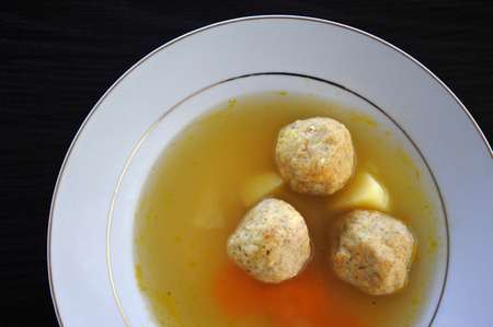 kneidl: Above view of Matzah balls, Ashkenazi Jewish soup dumpling made from a mixture of matzah meal, eggs, water and chicken fat served on Passover Jewish Holiday.Food background and texture Stock Photo