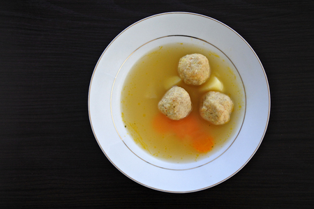 kneidl: Flat lay view of Matzah balls, Ashkenazi Jewish soup dumpling made from a mixture of matzah meal, eggs, water and chicken fat served on Passover Jewish Holiday.Food background and texture