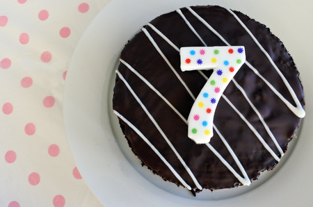 top seven: Flat lay view of a chocolate birthday cake for a seventh birthday or anniversary celebration. Life event concept. copy space