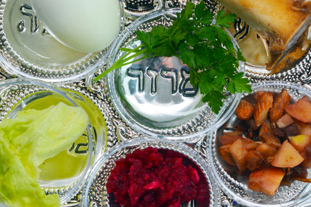 Passover Seder Plate with the seventh symbolic food items writing underneath them in Hebrew words used during the Seder meal on Passover Jewish holiday. Stock Photo