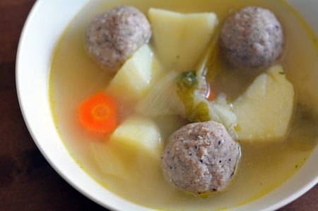 kneidl: Matzah balls, Ashkenazi Jewish soup dumpling made from a mixture of matzah meal, eggs, water and chicken fat served on Passover Jewish Holiday.Food background and texture Stock Photo