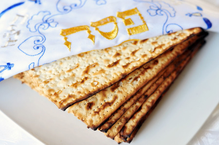 matzes: Passover or Pesach word in Hebrew with Matzo for Jewish Holiday Passover. Matzo is an unleavened flatbread part of Jewish cuisine of Passover festival. Food background and texture Stock Photo