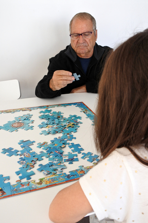 the grand daughter: Grandfather (man age 65-75) play with his granddaughter (girl age 07)  puzzle game at home. Real people. copy space