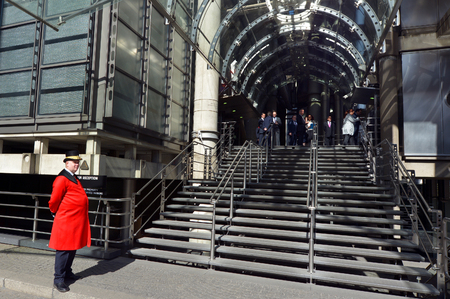 London, UK - May 13 2015: Security man supervisors the entrance to Lloyds insurance headquarter building entrance in City of London, UK. In 2012, Lloyds made a pre-tax profit of £2.77 billion on a record £25.50 billion of gross written premiums