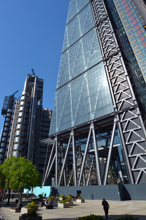London, UK - May 13 2015: Business people have a lunch break outside 122 Leadenhall Street tower and Lloyds building in City of London, UK. Both designed by the awarded British architectural firm Rogers Stirk Harbour and Partners.