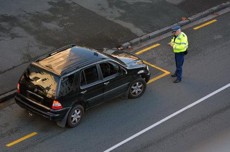 オークランド, ニュージーランド - 2017 年 6 月 8 日: 交通警察官交通引用道路の脇に車の運転手で書くオークランド市内中心部、新しいニュージーラ 報道画像