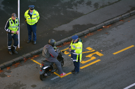 AUCKLAND, NEW ZEALAND - JUNE 08 2017: Traffic Police officer writing a traffic ticket to a scooter rider in Auckland city central, New Zealand. Traffic Police Monitor traffic to ensure motorists observe traffic regulations and exhibit safe driving procedu