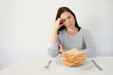 Young woman (age 25-35) suffers from a gluten. Gluten intolerant and Gluten free diet concept, Real people. Copy space