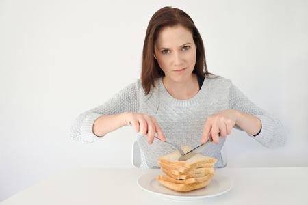 Jonge vrouw (leeftijd 25-35) geeft haar drang naar hun koolhydraten. Glutenintolerant en Glutenvrij dieetconcept, Echte mensen. Kopieer de ruimte