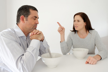 Mature man (age 40-45) suffers from his abusive partner (age 30-35). Emotionally abusive relationship concept. Real people. Copy space Stock Photo