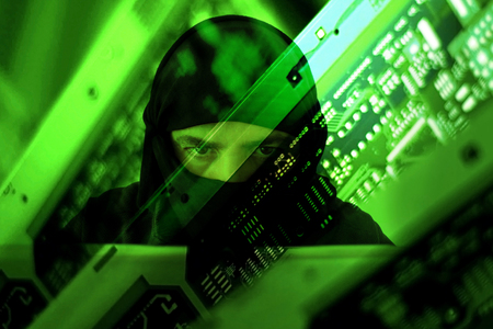 Hacker muslim terrorist committing violent act attack to achieve political gains through intimidation  of fear injury or harm from a laptop. Cyberterrorism concept. Real people. Copy space. Stock Photo