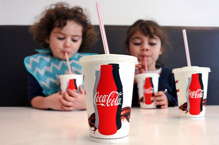 obesidad infantil: AUCKLAND - JULY 18 2017:Two young girls (Talya and Naomi Ben-Ari age 07- 03) drinking Coca Cola. Sugary drinks are a major contributor to health conditions such as obesity, diabetes and tooth decay.