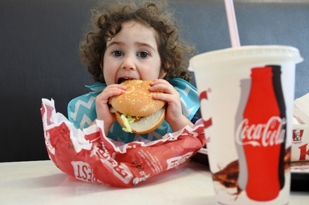 AUCKLAND - JULY 18 2017:Little girl (Naomi Ben-Ari age 03) eating fast food. Fast food is highly processed and contains large amounts of carbohydrates, added sugar, unhealthy fats, and salt (sodium).