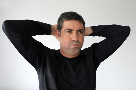 Upset man (age 40) holds his hands behind his head.  Real people. Anxiety concepts and ideas. Copy space Stock Photo