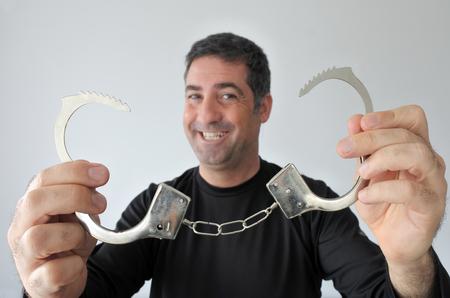 Een gelukkige vrije man (40 jaar) heeft onbeheerde handboeien voor de camera. Freedom concept. Echte mensen. Kopieer ruimte