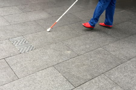 Unrecognisable Visually impaired person walks in the street with a long white cane stick