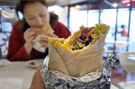 Close-up van de persoon eet Kebab Wrap Met Gegrilde Lam en Groenten. Stockfoto