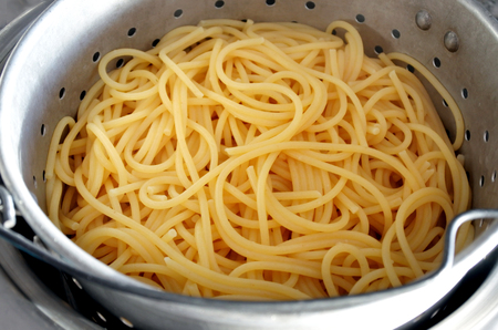 Cooked spaghetti noodles in a colander cooling down.