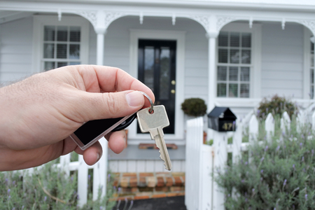 A mans hand holds a key against a front of a traditional villa house in Auckland, New Zealand. Buy, sale, real estate, insurance, mortgage, bank loans and housing market concept.