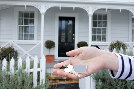 A womans hand holds a key against a front of a traditional villa house in Auckland, New Zealand. Buy, sale, real estate, insurance, mortgage, bank loans and housing market concept.