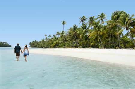 Couple Walk on One foot Island in Aitutaki Lagoon Cook Islands. Real people. Copy space