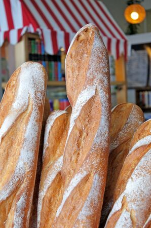 Fresh loafs of French bread outside a bakery in Paris, France. Baguette Bread. Food background and texture. Vertical cover Stock Photo