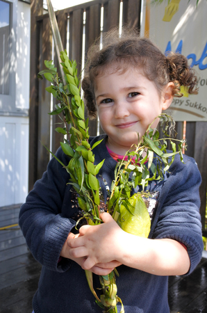 hadas: Jewish girl (age 03) blessing on the four spices on Sukkot Jewish Holiday.