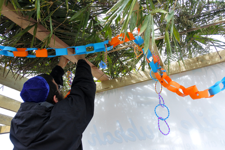 Jewish Orthodox man decorating a Sukkah on sukkot Feast of Tabernacles, Feast of the Ingathering or Feast of booths. Copy space
