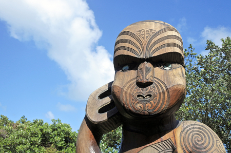 AUCKLAND - OCT 15 2017:Maori warrior wood carving statue in Karekare beach in the West Coast of the North Island near Auckland. Wood carving is a sacred art form for Maori native people of New Zealand