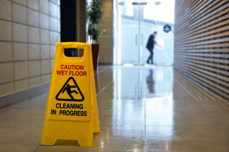 Slippery floor surface warning sign and symbol on a wet floor of unrecognizable building hallway.
