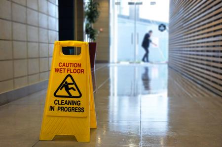 미끄러운 바닥 표면 경고 기호 및 인식 할 수없는 건물 복도의 젖은 바닥에 기호.