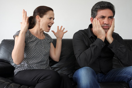 Nagging wife (age 30) complains to her husband (age 40) at home. Real people. Relationship lifestyle. Copy space Stock Photo
