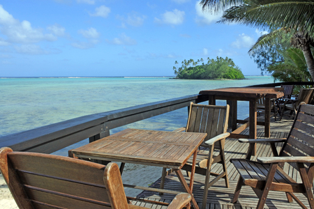 Landscape view of outdoors chairs and tables against  Taakoka islet in Muri Lagoon in Rarotonga, Cook Islands. Stock Photo